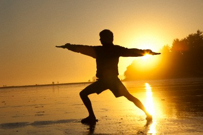 A male performs yoga on the beach at sunset in  British Columbia