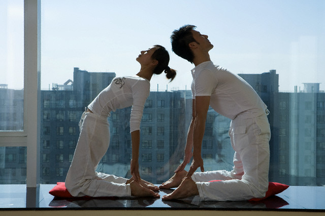 Couple Doing Yoga by Window