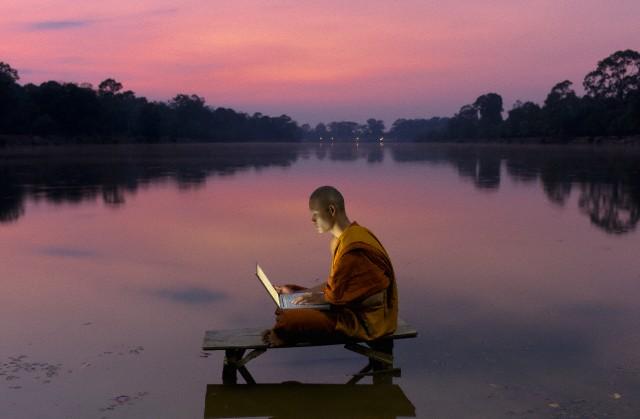 Buddhist Monk using laptop computer