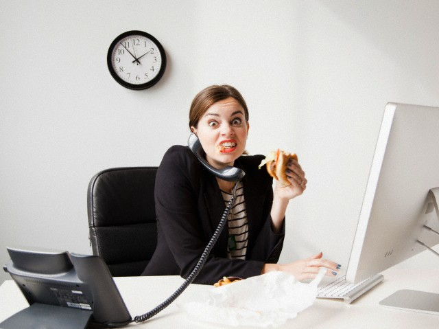 Studio shot of young woman working in office and having lunch same time