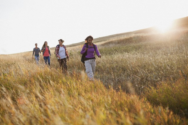 Four women with backpacks following each other in field.