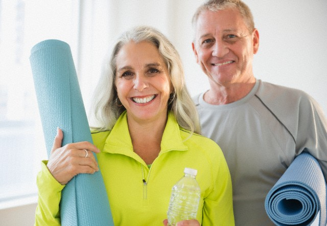 Portrait of mature couple holding yoga mats