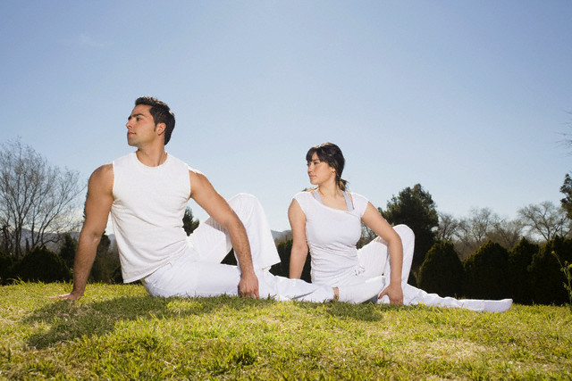 Couple Practicing One Leg Revolving Seated Pose