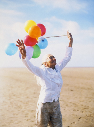 Senior Woman Holding Toy Balloons at Beach