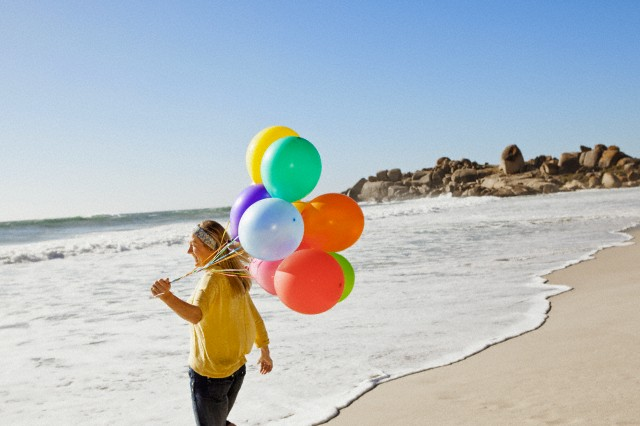 Smiling mature woman holding balloons on beach