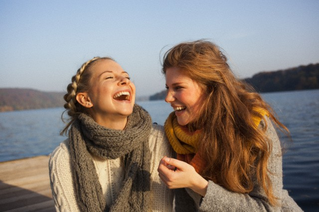 Two young women sharing leisure time at lake