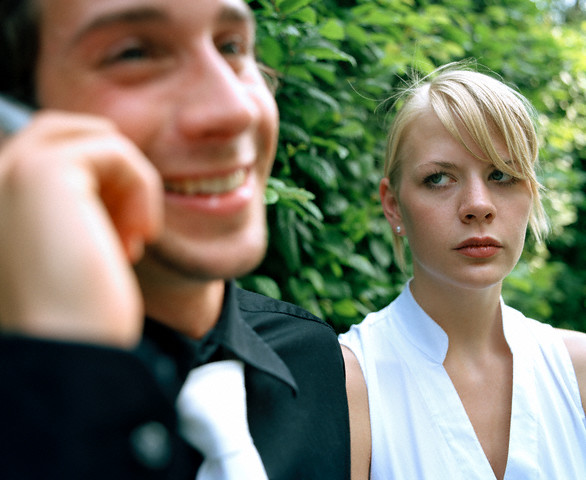 Woman looking at man using mobile phones