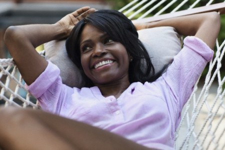 Middle-aged woman smiling while lying in hammock.