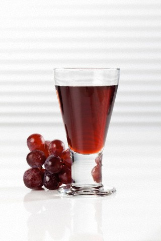 Glass of red grape juice beside grapes, close up