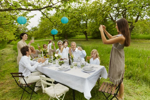 Woman taking picture of family and friends dining al fresco