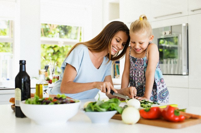 Mother and daughter (4-5) preparing food in kitchen