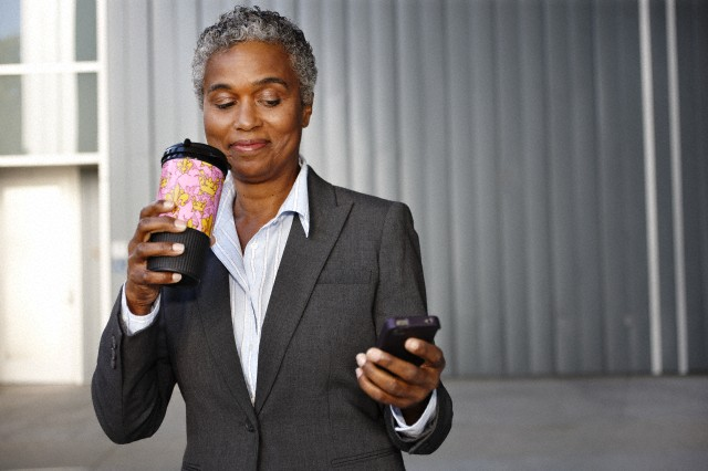 Businesswoman holding coffee and texting
