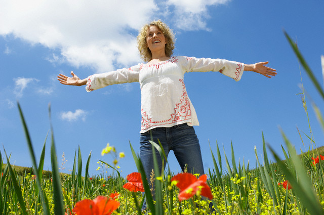 Woman in Meadow with Arms Outstretched