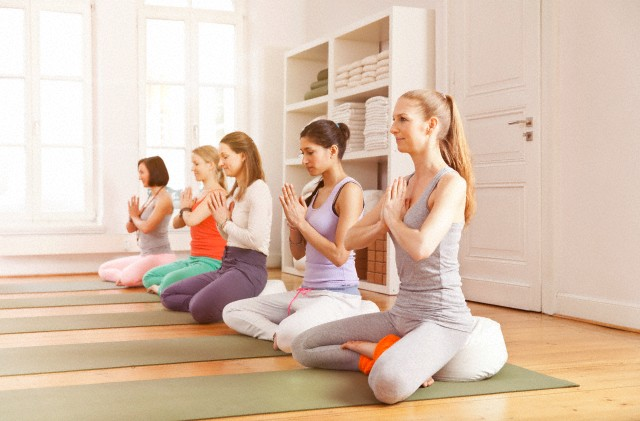 Group of mid adult women exercising in yoga studio