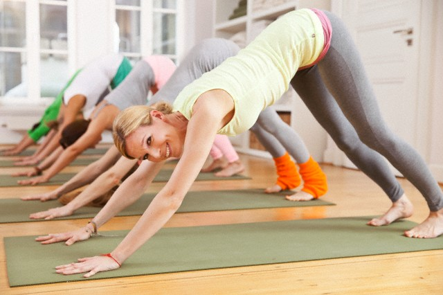 Group of mid adult women doing downward-facing dog pose in yoga studio