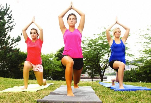 Three women practising yoga outdoors