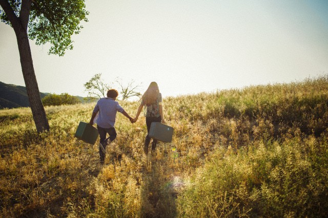 Young adult couple with suitcases walking in field