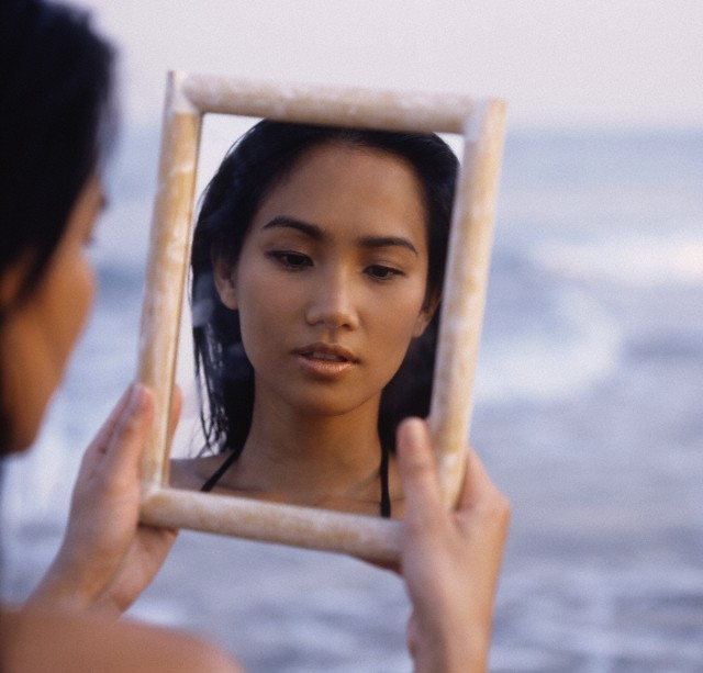Woman in a mirror by the sea