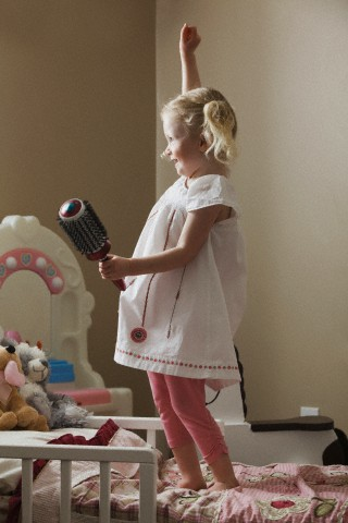 Young girl dancing,her bed