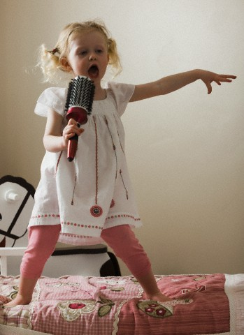 Young girl singing,her bed