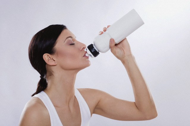 Mid adult woman drinking from water bottle against white background