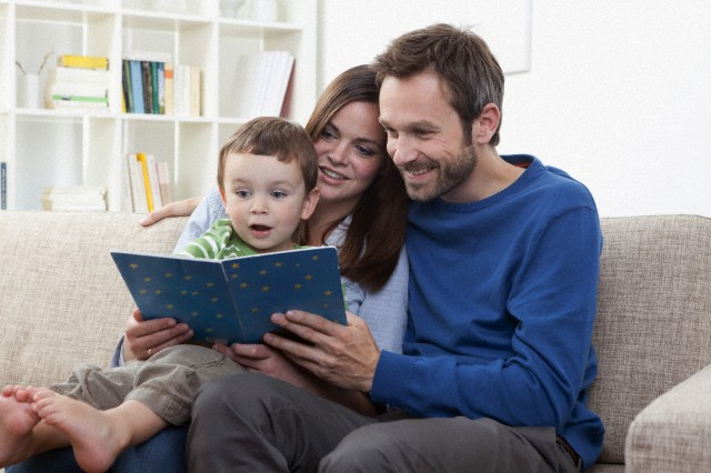 Germany, Bavaria, Munich, Parents reading book with son (2-3 Years) in living room
