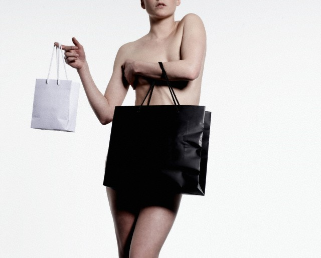 Studio shot of naked woman covering herself with shopping bag
