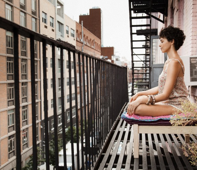 Young woman meditating on balcony facing street below