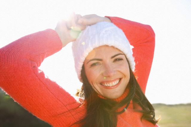 Smiling Woman with Hands on Head Wearing Wool Hat