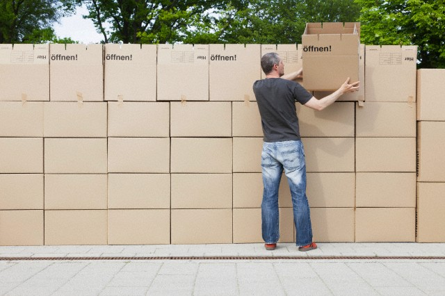 Man building wall of cardboard boxes