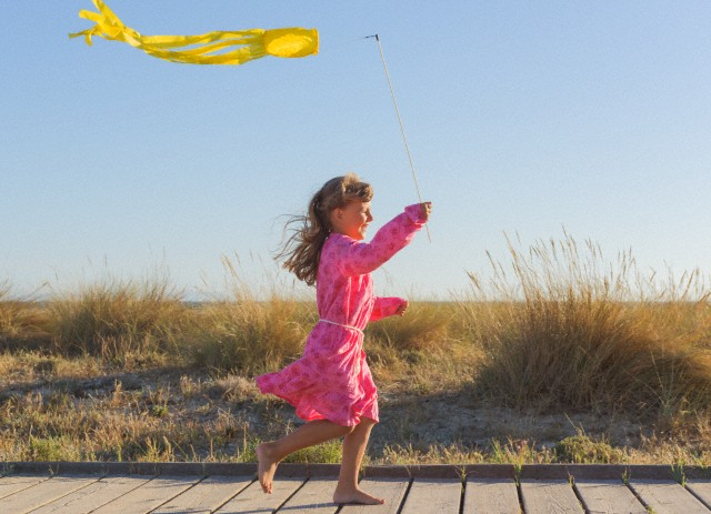 Young girl playing with a kite.